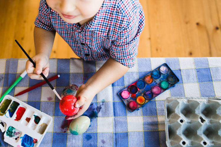 Midsection of boy painting easter egg at home
