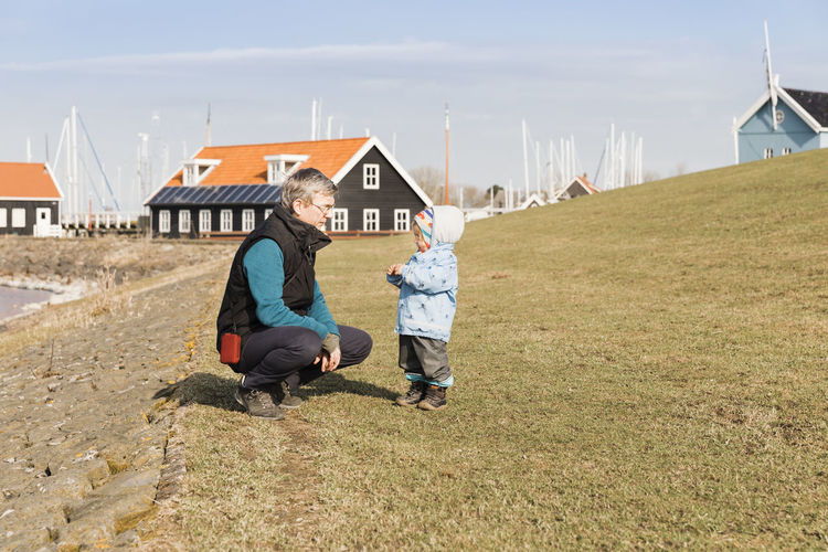 Mature man with toddler girl on dyke – Hindeloopen, Netherlands, Europe Grandfather Grandchild Multi-generation Family Granddaughter Generations Offspring Family❤ Crouching Netherlands Dyke  Friesland Hindeloopen Rural Scene Portrait Mature Adult Mature Men This Is Masculinity Child Childhood Toddler  Girl Childhood Memories Standing Care Warm Clothing