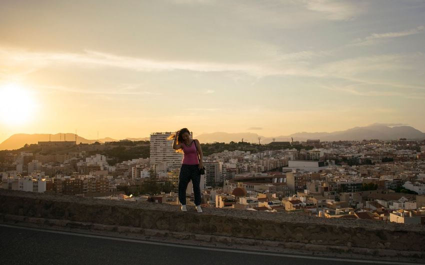 Woman Standing Against Cityscape During Sunset
