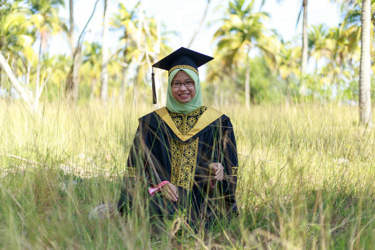 Portrait Of Smiling Young Woman Wearing Graduation Gown While Standing On Field