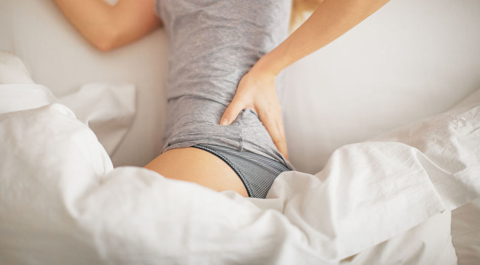 Woman in bed with backache Pants Pharmacy Abdomen Ache Adult Articulation Backache Bad Sleep Bed Bedroom Close-up Human Body Part Human Leg Indoors  Insomnia Low Section Lying Down Period Physiotherapy Pill Postural Relaxation Young Women