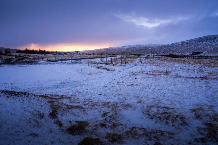 Scenic view of snowcapped field against sky during sunset