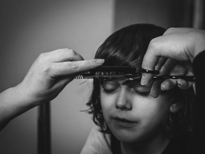 Close-up portrait of a boy having hair cut