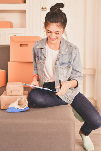 Box Cardboard Cardboard Box Casual Clothing Front View Hairstyle Happiness Holding Indoors  Jeans Lifestyles Moving House One Person Packing Real People Sitting Smiling Three Quarter Length Wireless Technology Women Young Adult Young Women