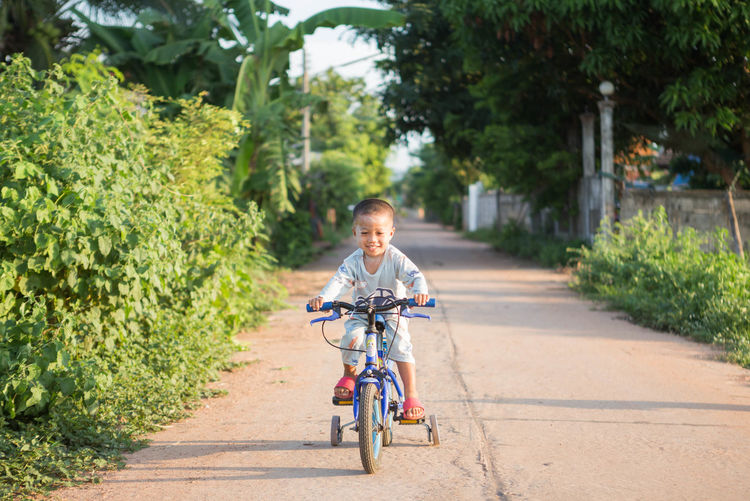 Smiling boy riding bicycle on road