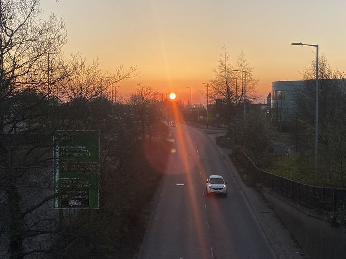 Cars on road against sky at sunset