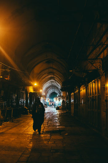Rear view of man walking on illuminated footpath at night