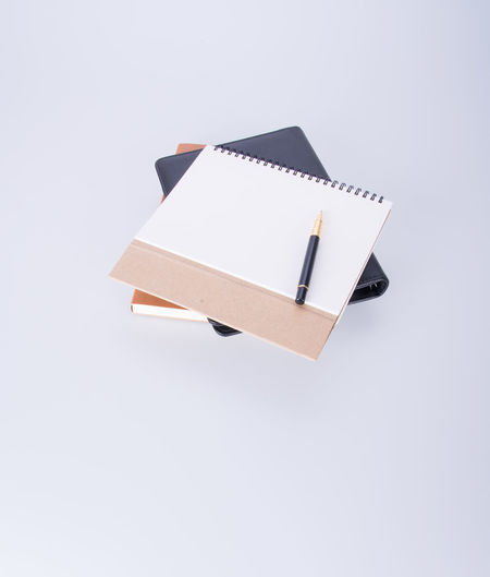 High angle view of books with pen on white background