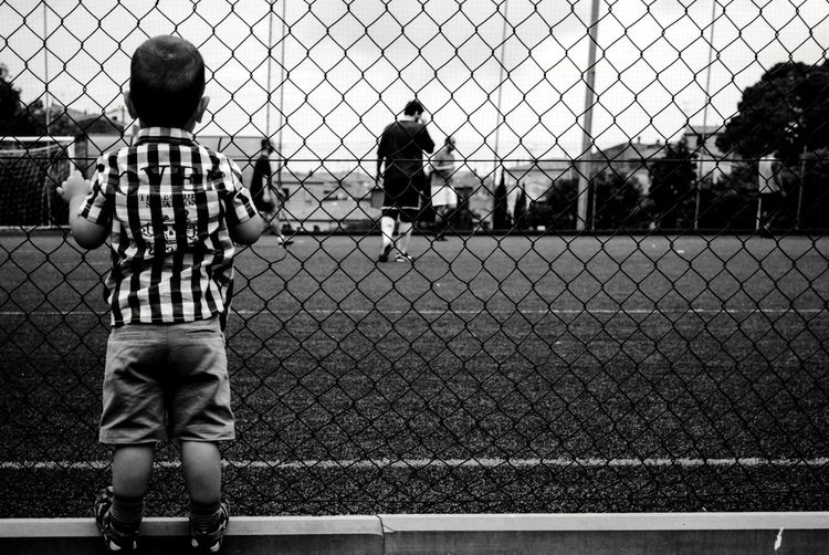 Rear View Of Boy Watching Soccer Through Chainlink Fence