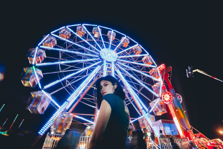 Amusement Park Amusement Park Ride Illuminated Night Arts Culture And Entertainment Ferris Wheel Leisure Activity Low Angle View Spinning Standing Motion Architecture Enjoyment Sky One Person Real People Casual Clothing Three Quarter Length Fun
