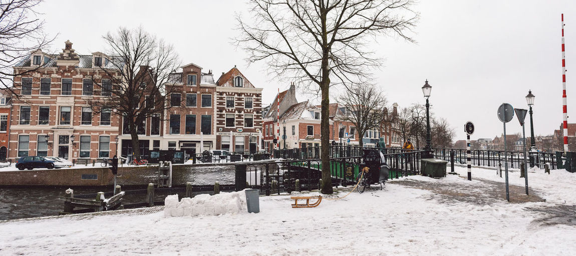 Snow covered canal by buildings against sky