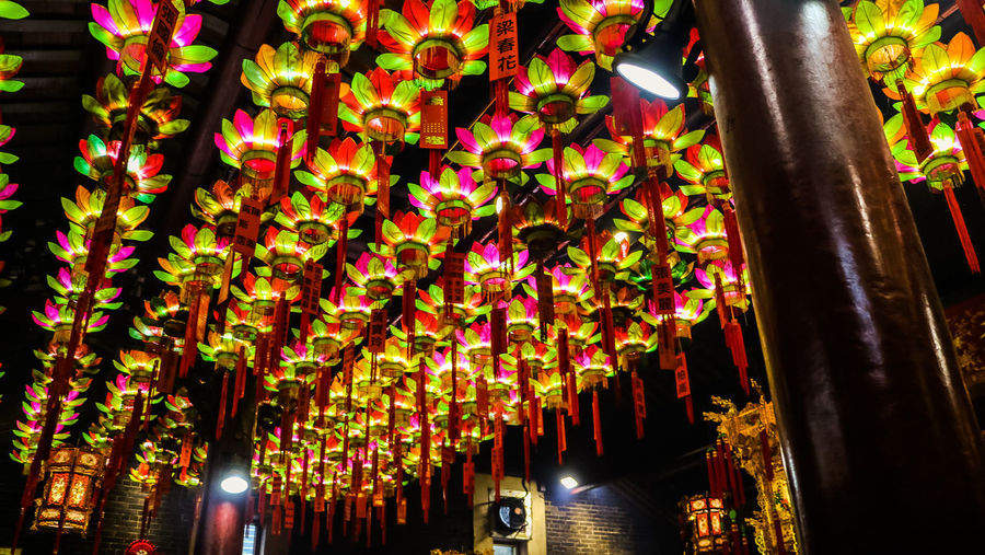 Low angle view of illuminated lanterns hanging on ceiling of building