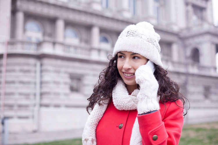 Young woman in warm clothing talking on smart phone while standing on city street