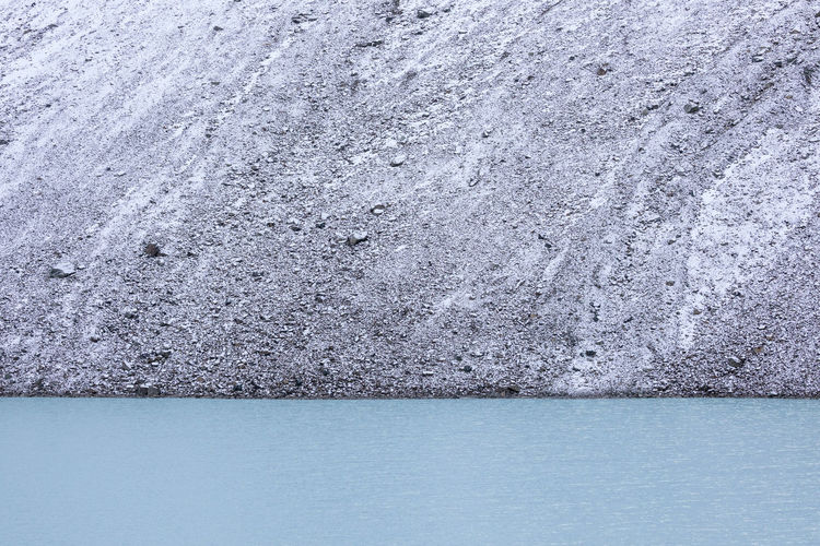Glacial lake in the mountains against steep screes Cold Temperature Snow Arctic Outdoors Water Textured  Abstract Backgrounds Blue Gray Extreme Terrain Waterfront Close-up Beauty In Nature Nature Full Frame Backgrounds Day No People Lake Glacier Lagoon Rock Formation Mountain Remote Scree Steep