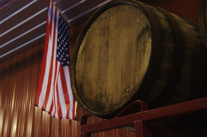 A barrel with an American flag behind it American American Flag America Barrel Distillery Flag Indoors  No People Whiskey Whiskey Barrels Wine Cask Wood - Material