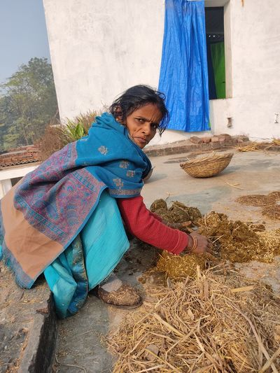Full length of woman collecting cow dung outdoors