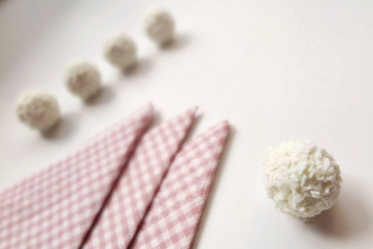 High angle view of grated coconut balls by napkins on table