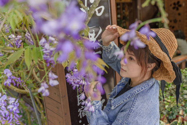 High angle view of woman looking at purple flowering plants