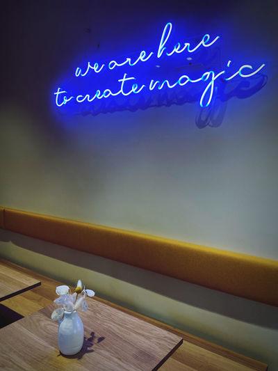 Illuminated text on blue table against sky