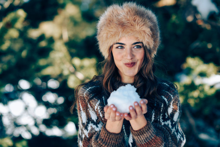 Beautiful woman holding snowball while standing against tree