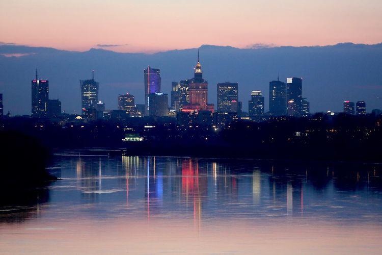 River leading towards illuminated city at night