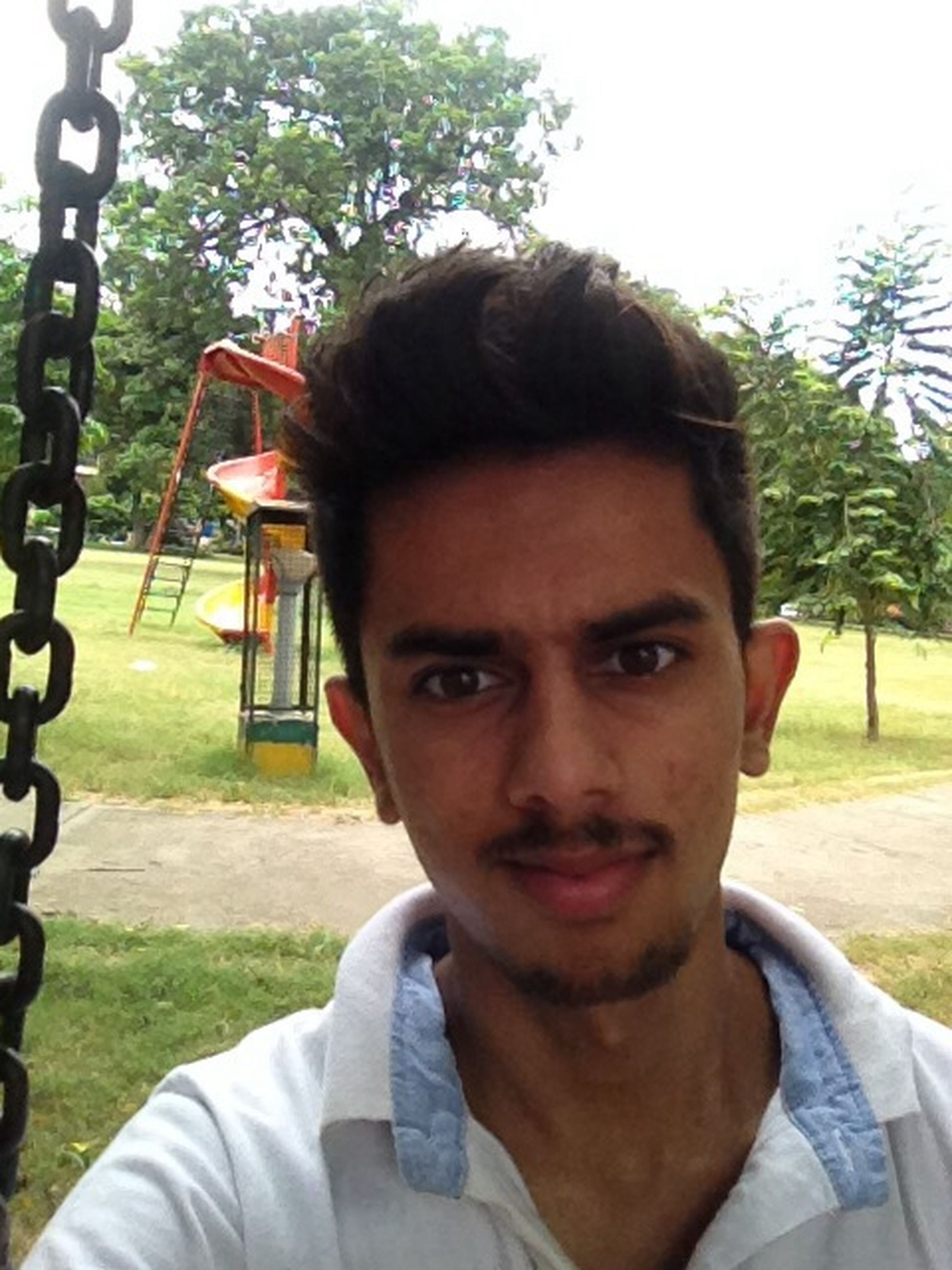 looking at camera, portrait, headshot, person, front view, lifestyles, young adult, leisure activity, tree, young men, close-up, smiling, head and shoulders, park - man made space, focus on foreground, day, casual clothing, outdoors