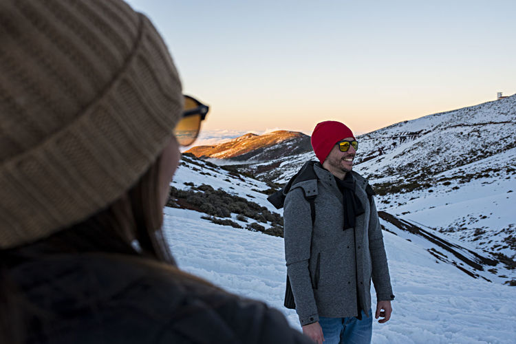 Friends in sunglasses standing on snow covered mountains against sky