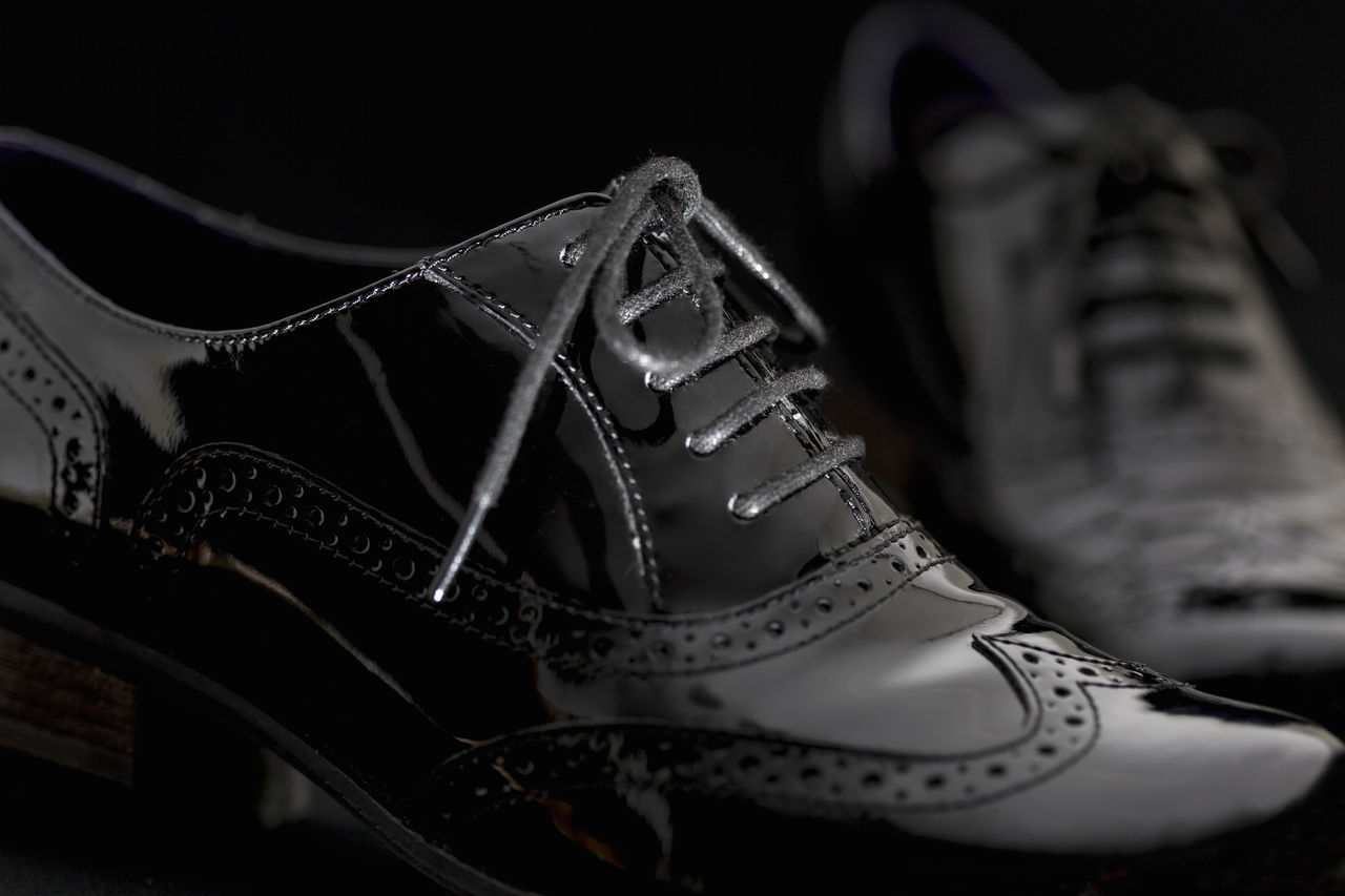 shoe, indoors, close-up, shoelace, selective focus, pair, no people, canvas shoe, still life, white color, lace - fastener, black background, focus on foreground, fashion, black color, sports shoe, personal accessory, clothing, sport, pattern, leather, compatibility