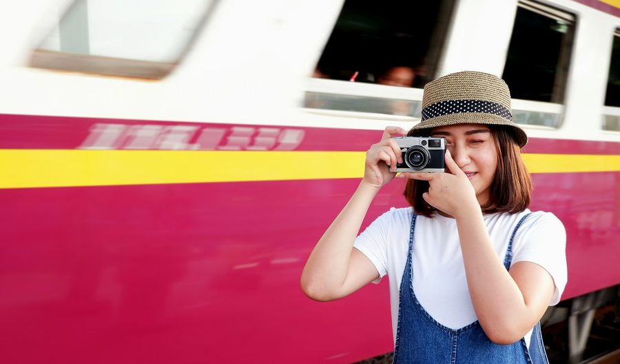 Young pretty female tourist taking photo with vintage camera and blurred background of train running through out the station, lifestyle in travel concept Lifestyle Pretty Woman Casual Vintage Style Taking Photo Camera Travel Train Station Space Blurred Background Asian  Lovely Smiling Happiness Outdoors Hat Thai EyeEm Selects Young Women Portrait Beautiful People Beauty Beautiful Woman Females Youth Culture Railroad Station Public Transportation Railroad Station Platform Rail Transportation