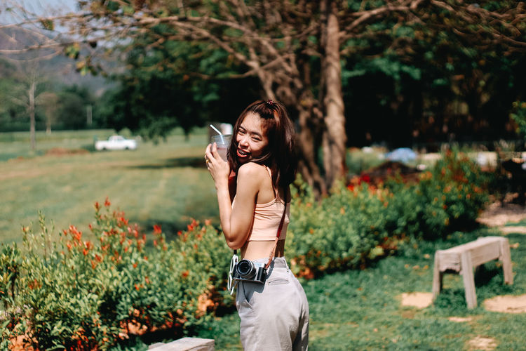 Young woman photographing with mobile phone while standing on plants