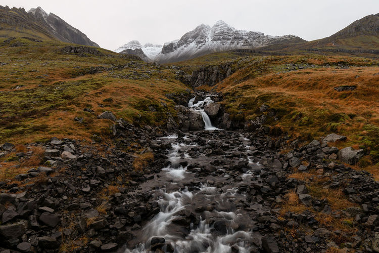 Scenic view of waterfall against mountain
