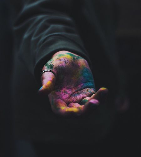 Close-up of human hand with colorful powder paint