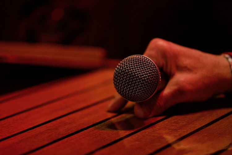 Cropped Hand Holding Microphone On Table