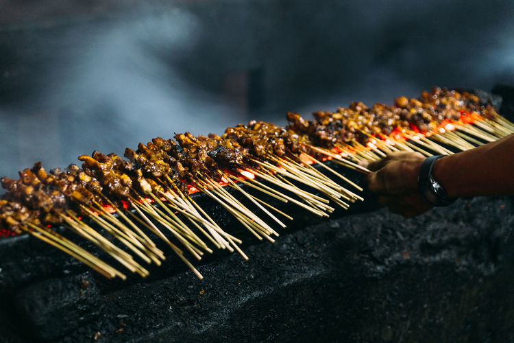 Cropped hand making meat on barbecue
