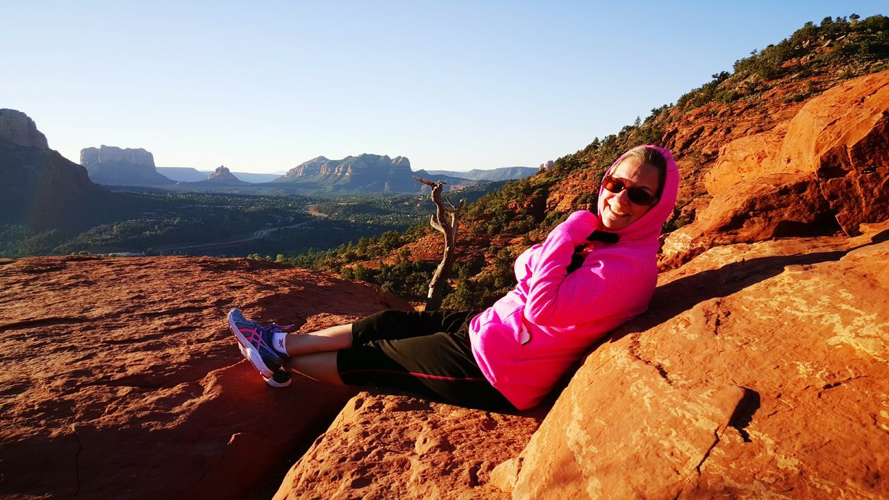 real people, lifestyles, leisure activity, rock - object, one person, young adult, rock formation, young women, mid adult women, nature, sunlight, full length, beauty in nature, outdoors, day, mountain, healthy lifestyle, looking at camera, exercising, shadow, sports clothing, scenics, smiling, water, sky