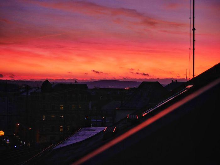 Silhouette city against orange sky