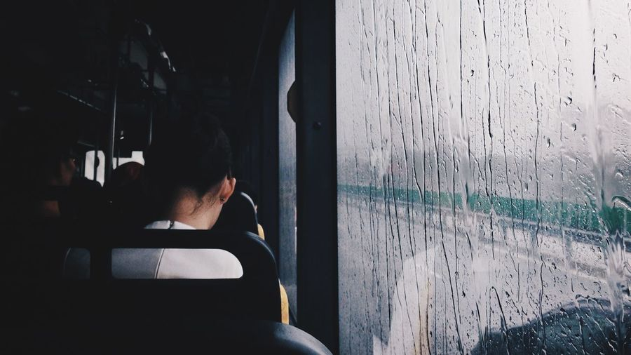Rear view of woman relaxing by wet window in bus during rainy season