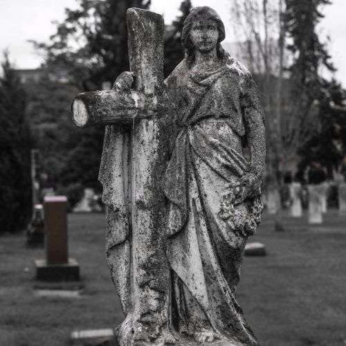 Close-up of statue in cemetery against sky