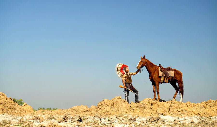 Full length of man wearing costume with horse against sky