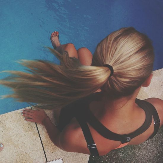 Full length rear view of woman sitting by swimming pool