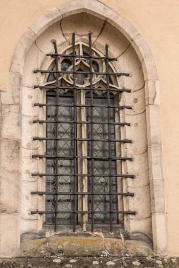 Old historical building with a lattice made of steel in front of the window Architecture Built Structure Building Exterior Building Day Arch Place Of Worship History No People The Past Religion Low Angle View Old Window Wall Outdoors Belief Spirituality Architectural Column Gothic Style