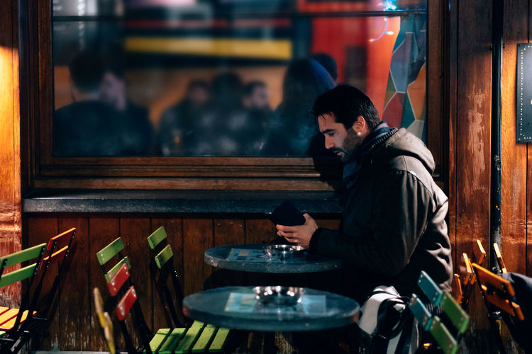 One man sitting at a cafe terrace using mobile phone