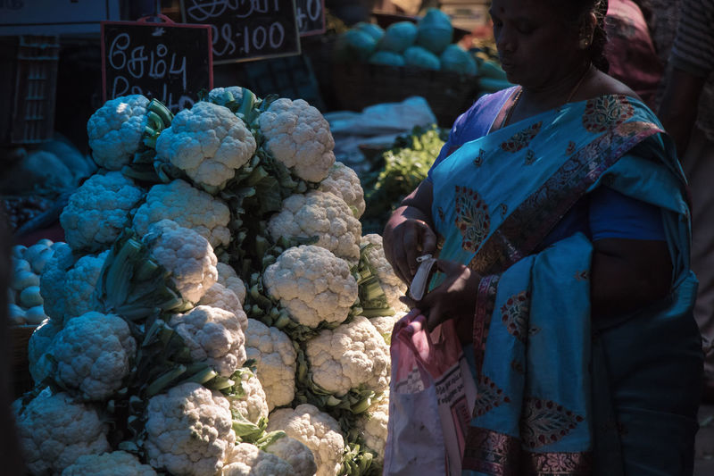 Midsection of woman for sale at market stall