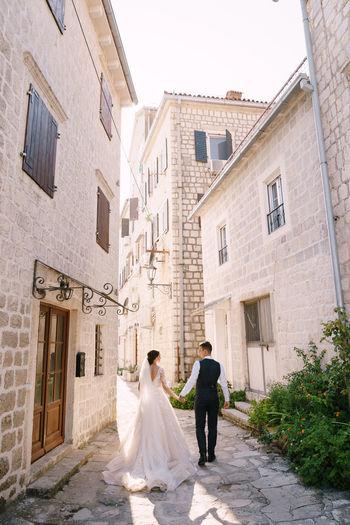 Rear view of couple walking on cobblestone street