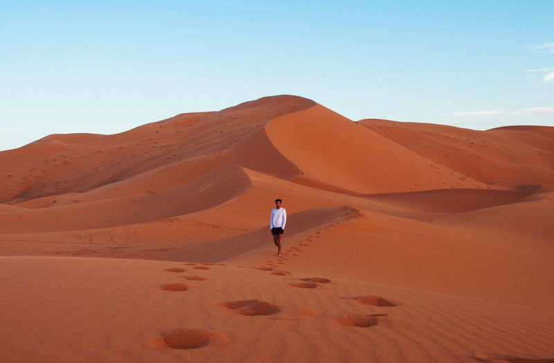 Man walking on sand dune at sahara desert against sky
