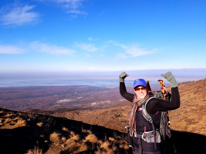 Portrait of happy female hiker wearing sunglasses while standing on mountain against sky