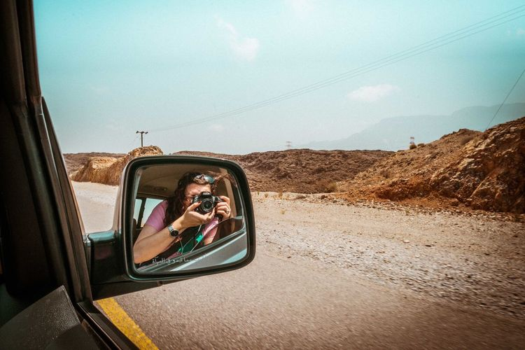 Oman Chapters Transportation Mode Of Transportation Sky Car Side-view Mirror Travel Land Vehicle Reflection Road Motor Vehicle Road Trip Day Technology Nature Young Adult Vehicle Interior Leisure Activity One Person Journey Portrait Outdoors