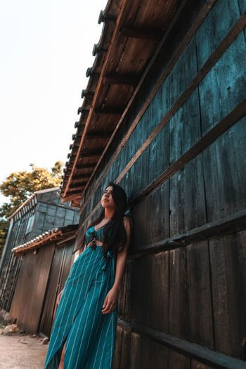 Woman leaning on wall of house