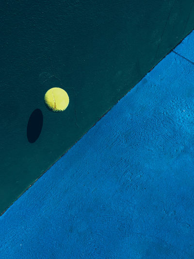 High angle view of yellow ball in blue water