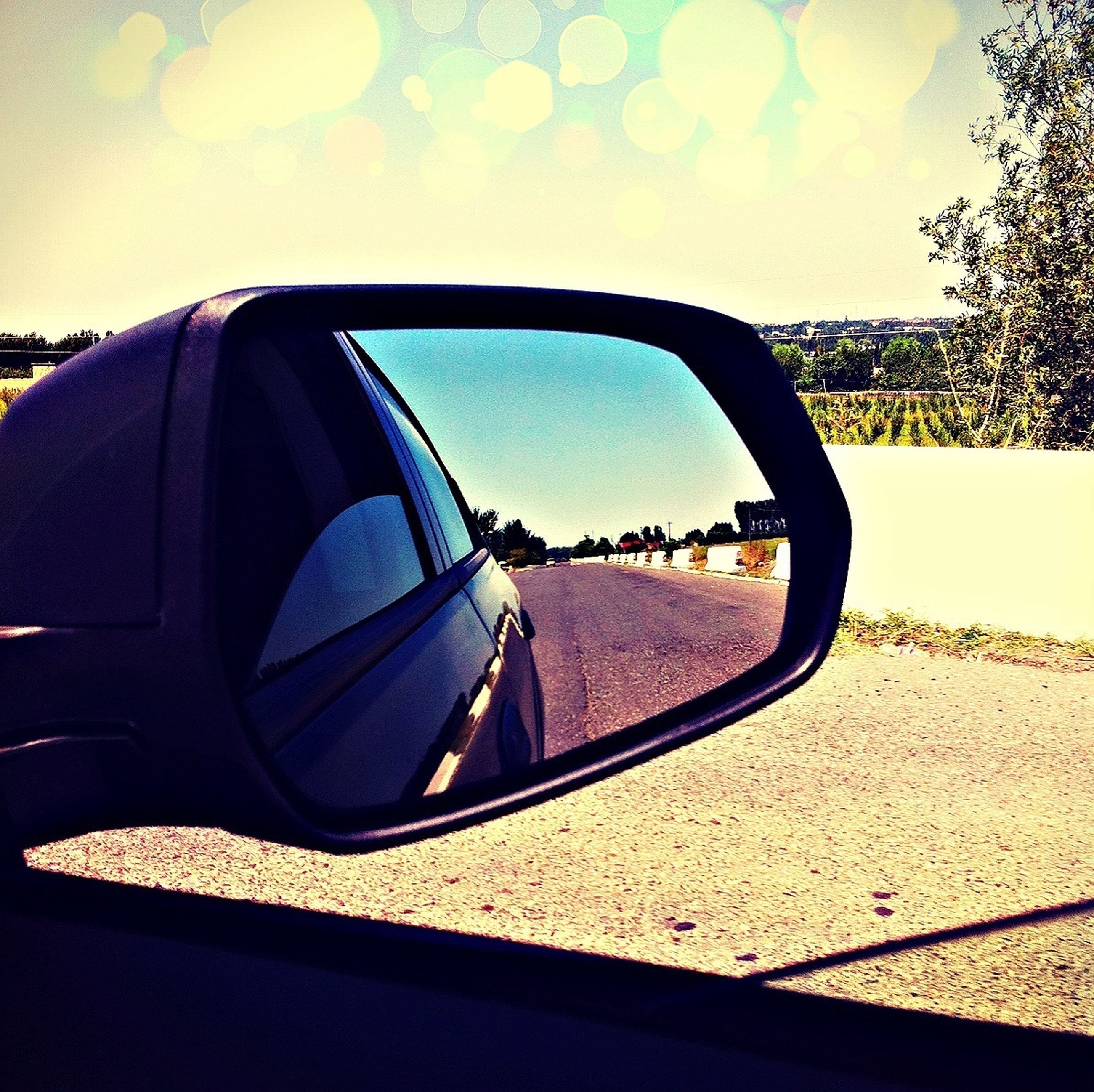transportation, mode of transport, land vehicle, car, side-view mirror, sky, close-up, part of, vehicle interior, clear sky, reflection, sunlight, landscape, cropped, road, day, travel, car interior, sunglasses, bare tree